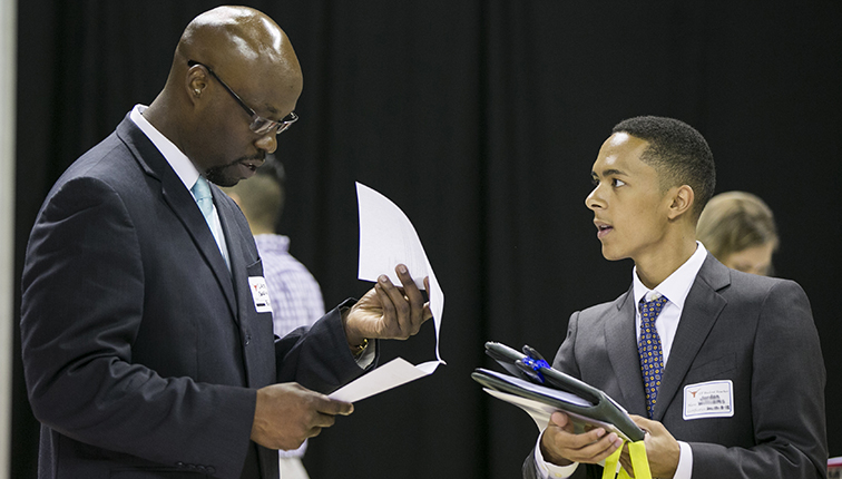A recruiter looks over a student's resume as the student looks on