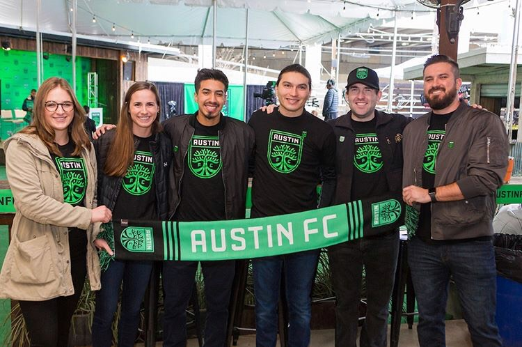 Graduate students holding an Austin FC flag