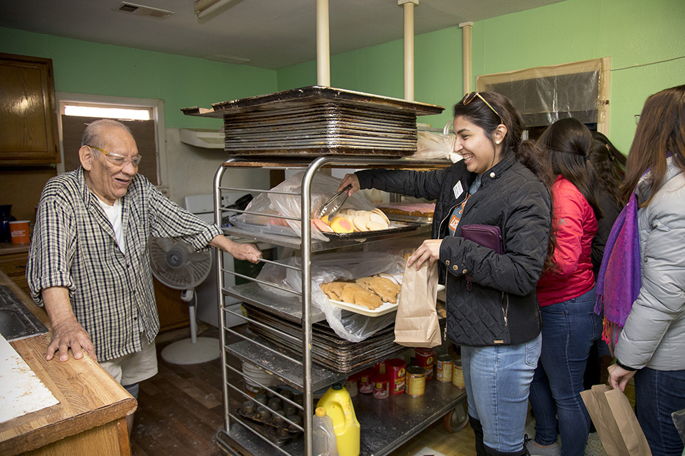 A group of people gather in a Hispanic bakery.