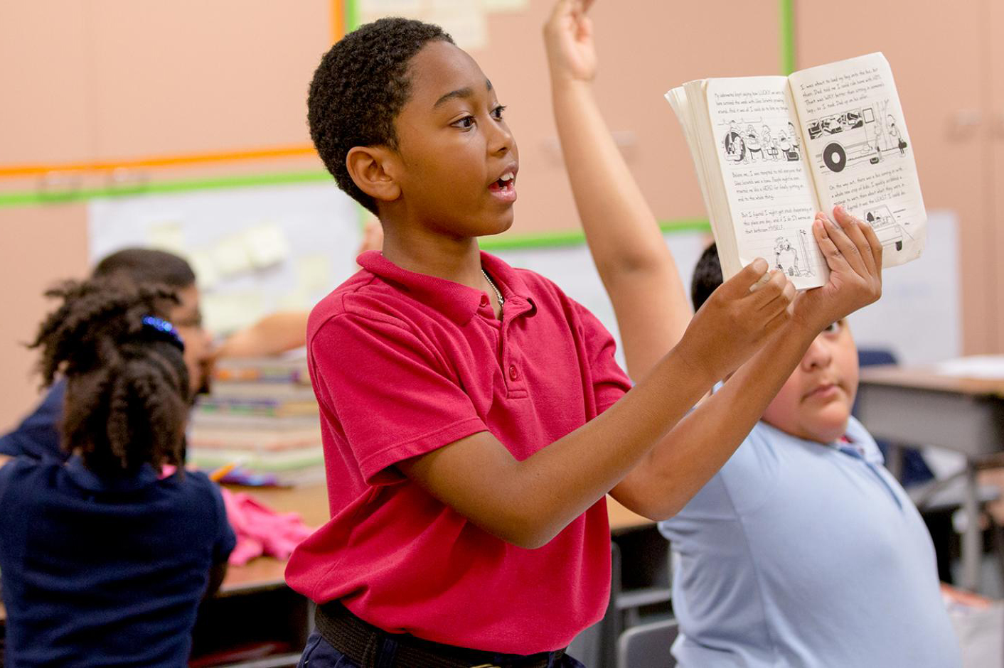 A black boy stands and holds up a book while his classmates look on