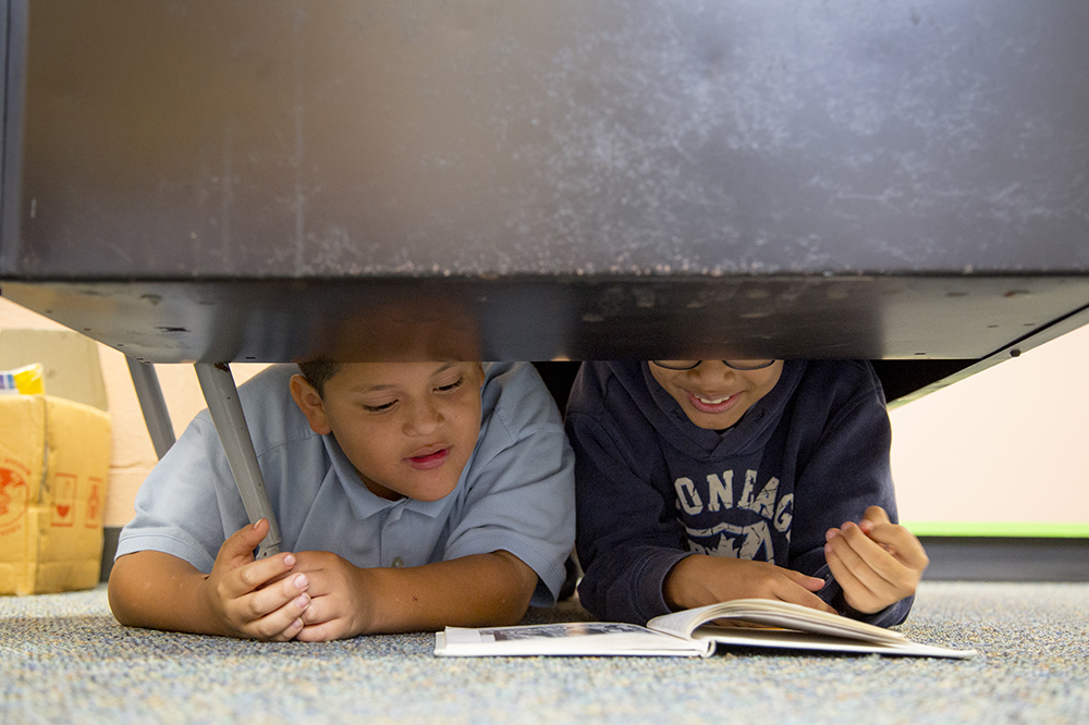 Two boys read a book together.