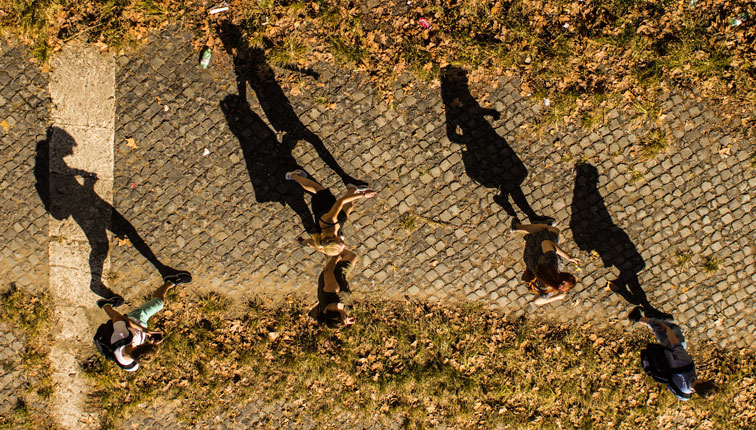 People walking with shadows on brick road