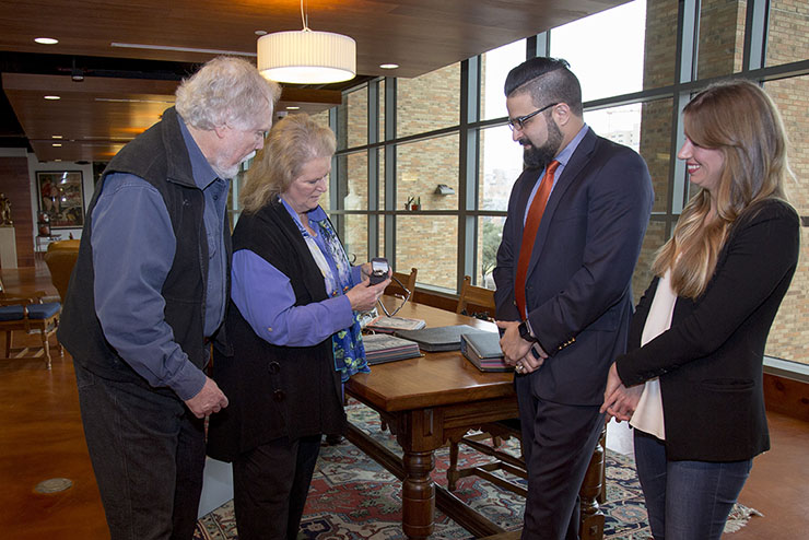 Jan and Terry Todd, of the Stark Center, take a close look at the ring while Soroush Abboud and Christina Cole look on.