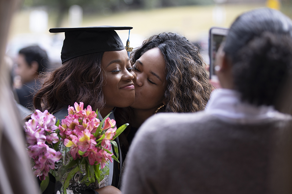 A recent Texas Education graduate is embraced by her family.