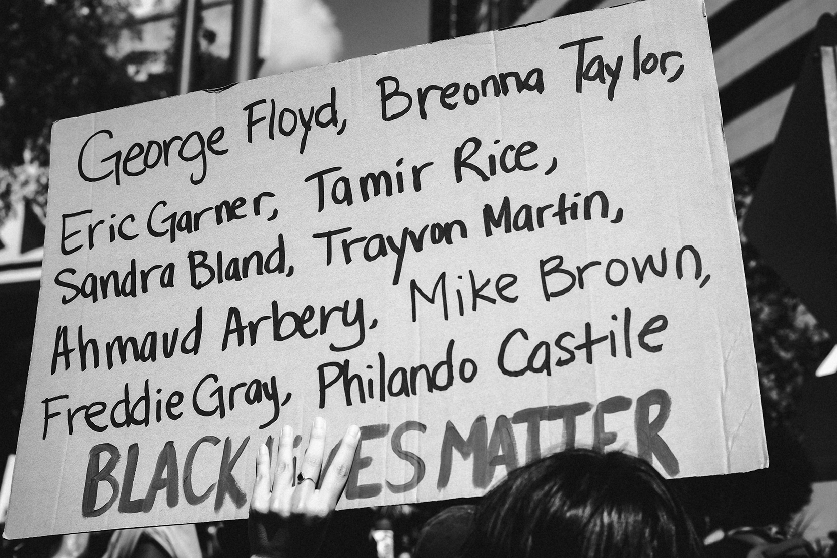 A protestor holds a sign listing the names of those killed, including George Floyd, Breonna Taylor, Eric Garner, Tamir Rice, Sandra Bland, Trayvon Martin, Ahmaud Arbery, Mike Brown, Freddie Gray, Philando Castile. Black Lives Matter
