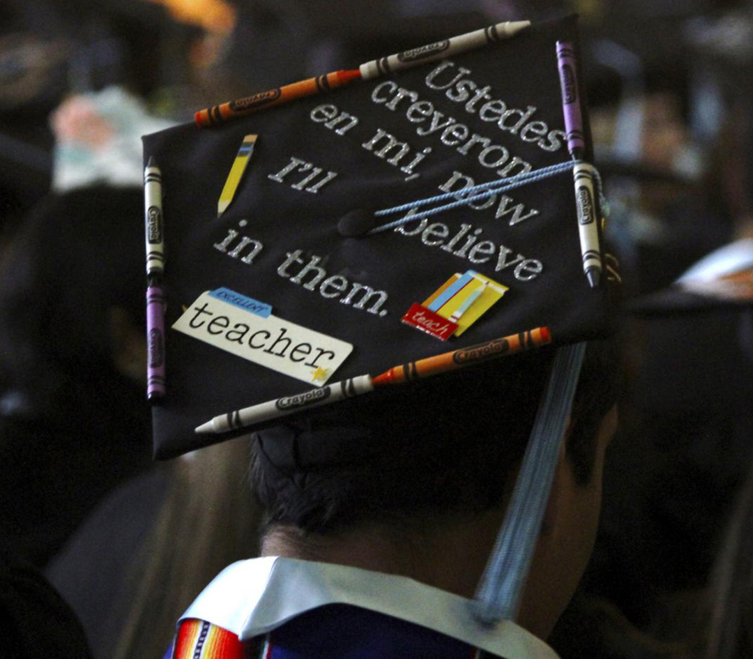 A young man wears a graduation cap decorated with the phrase: Ustedes creyeron en mi, now I'll believe in them.
