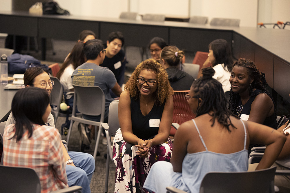 Diverse groups of incoming graduate students meet at orientation.