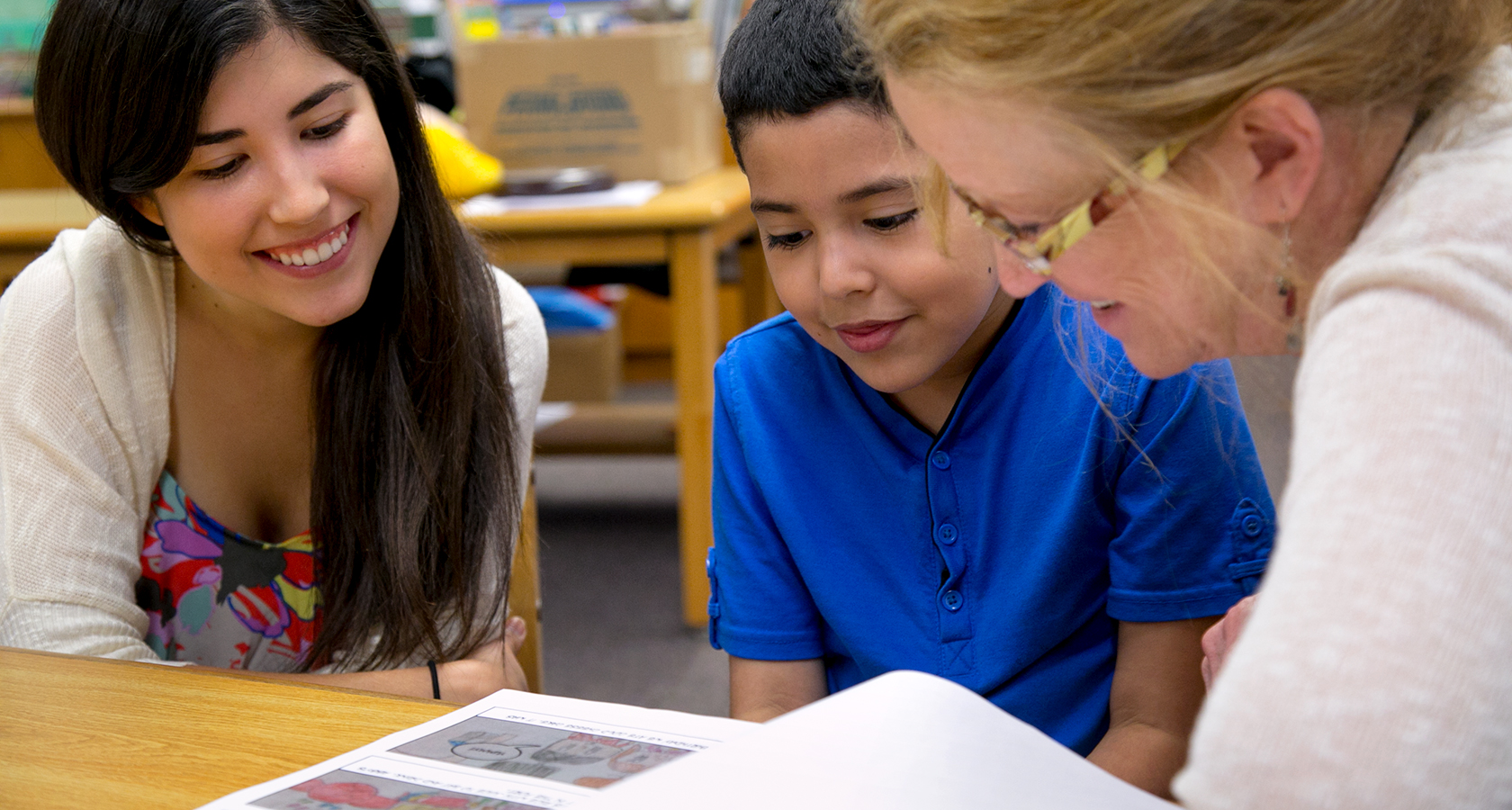 A young student teacher smiles as sits with a boy while a faculty member shows them a reading passage.