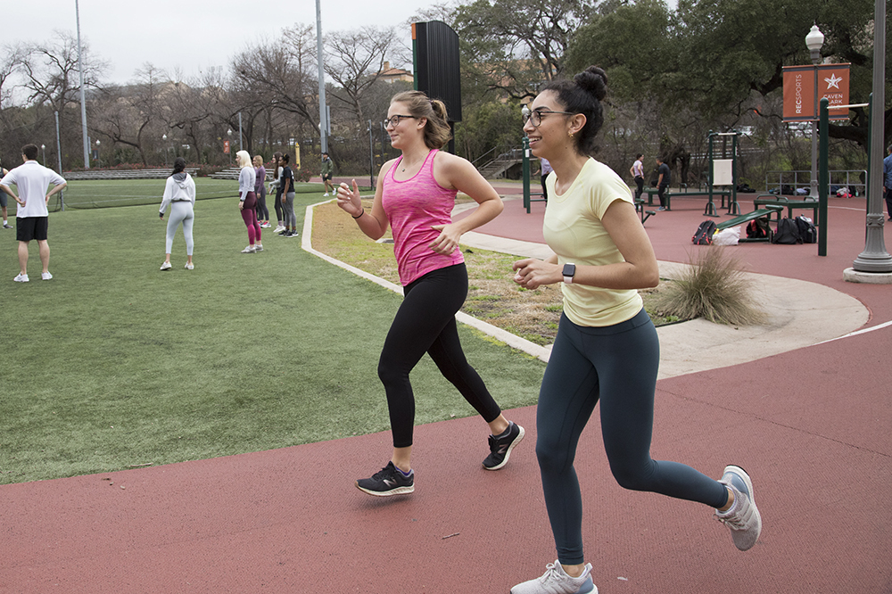 Two women jog around a track while others play soccer in the background.