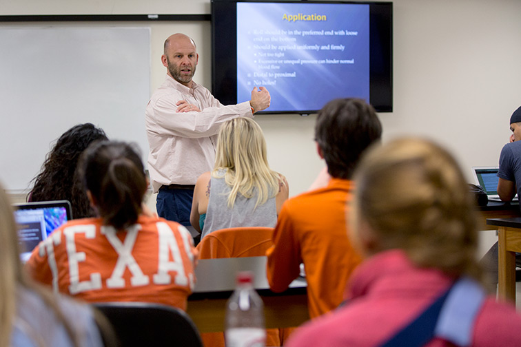 Students listen to a Corey Hannah give a presentation in a classroom setting.
