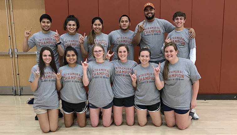 "A group of 11 students of different ethnic and racial backgrounds wearing ""Intramural Champions"" t-shirts hold up their hands in the ""hook 'em horns"" sign."