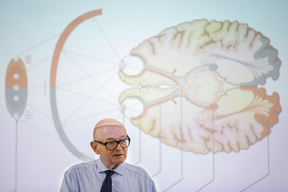 Steven Kornguth stands in front of an illustration of the human brain