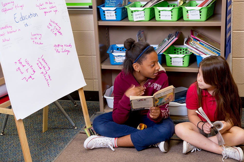 Two girls discussing the books they are reading.