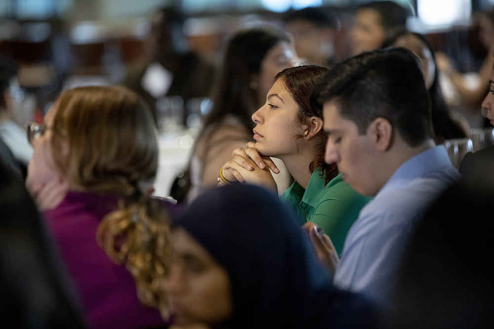 A young woman listens to a presentation.