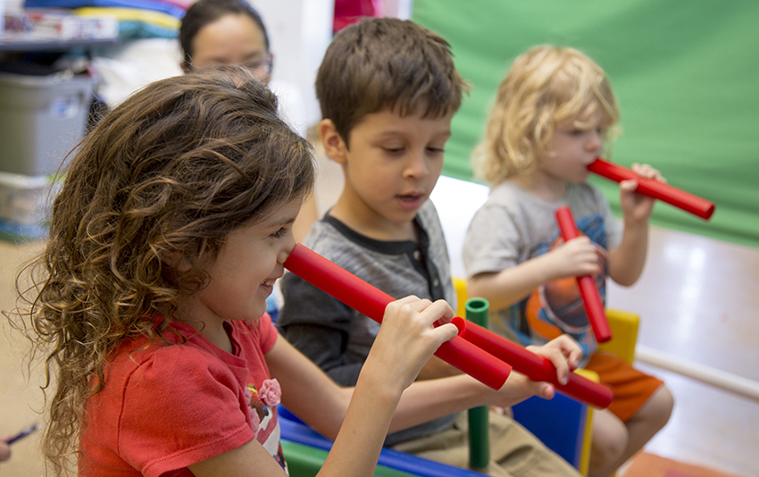 pre-k children play with red batons in a classroom.