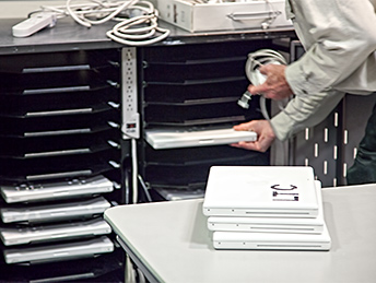 A man loads laptops into a cart