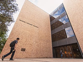 Photo of a student walking up to the entrance of the George I. Sánchez building, home of the College of Education