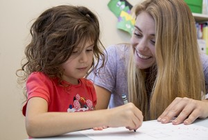 A young girl colors while her teacher looks on.
