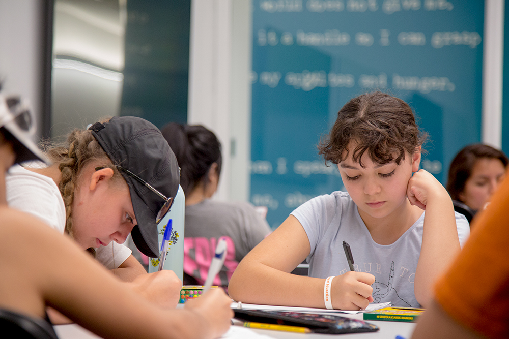 Two girls participate in a writing exercise