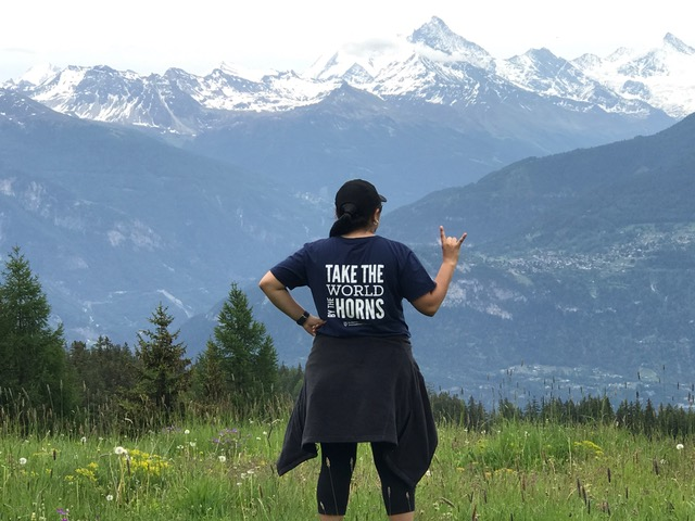 "A young woman wearing a t-shirt reading ""Take the world by the horns"" stands in front of a mountain landscape"
