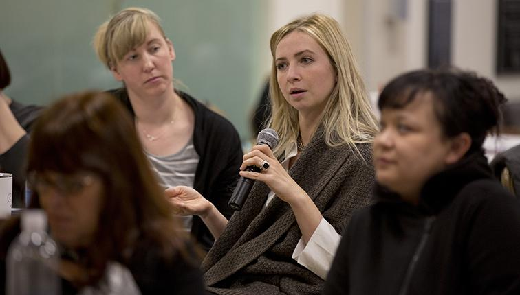 A woman sitting at a table asks a question during a recent conference on autism.