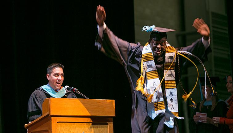 A young man raises his arms in joy as he walks across the stage during the last commencement ceremony.