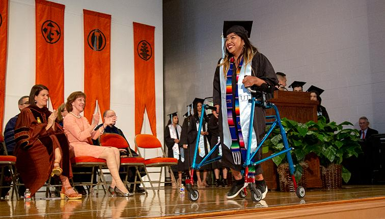 A recent graduate crosses the stage with the help of a walker.