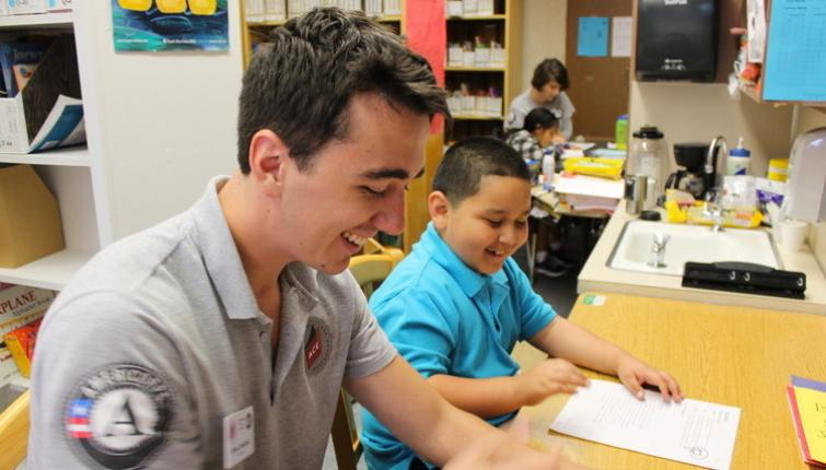 A young man works with a student. Both are smilling