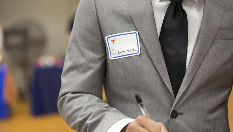 A young man in a gray suit takes notes.