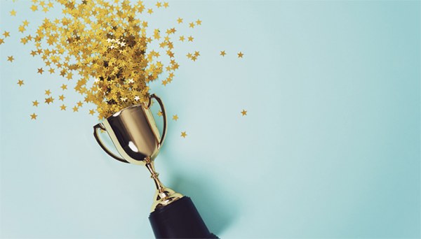 Photo of a trophy with gold star confetti shooting out of it.