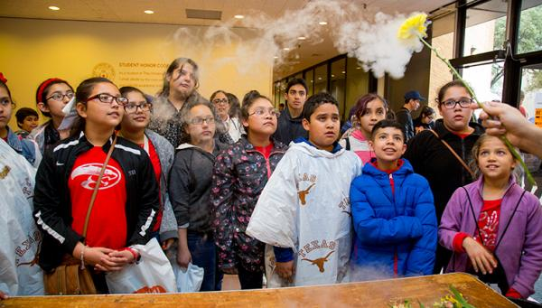 Children look on as a faculty member prepares to smash a flower frozen with liquid nitrogen.