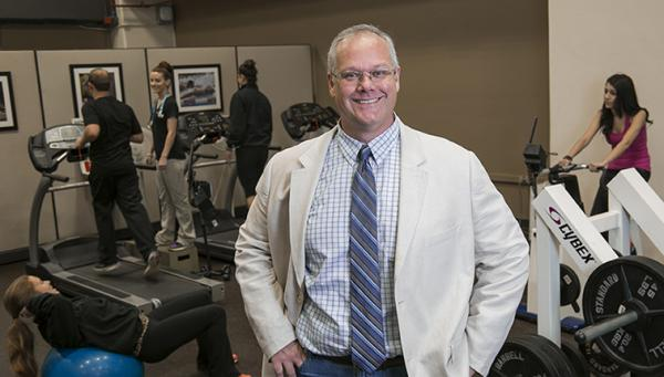 Photo of Dr. John Bartholomew standing in a gym while others work out.