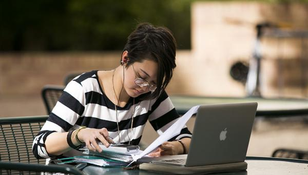 A young woman studying with her laptop open.