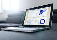 Photo of a laptop with the monitor showing different forms of data visualization
