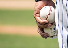A man holds two baseballs in his left hand.