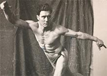 Old black-and-white photo of a man posing with his arms outstretched in a balletic posture.