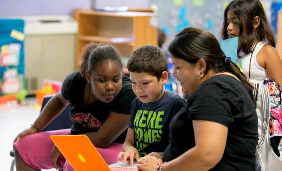 A young Latina teacher works with a latino boy on a laptop while a black girl and a Latina girl look on.