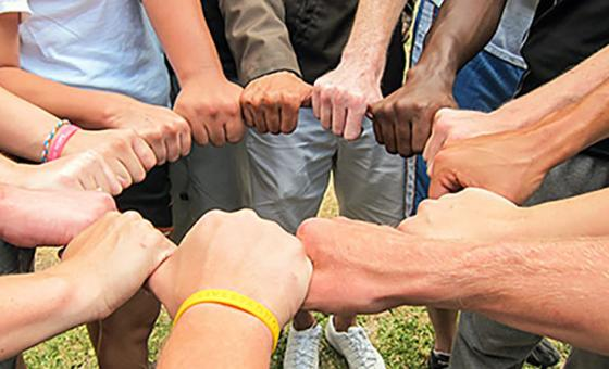 Several people stand in a circle and form a ring with their hands.