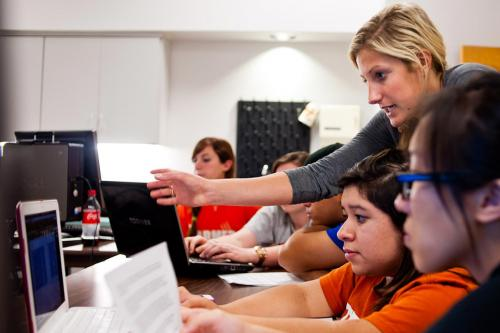 Teacher instructing students on computer