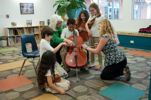 Two teachers and several students surround a young boy with a cello.