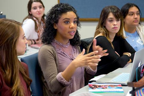 A young woman discusses a point in class as other students listen.