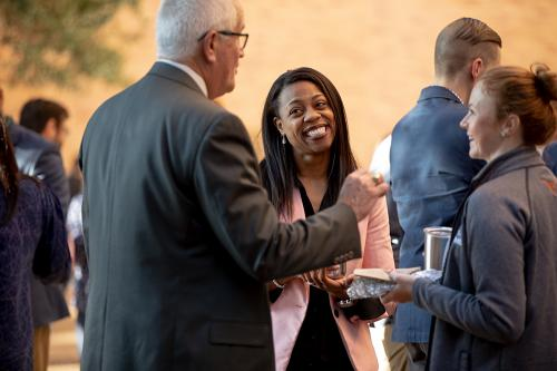 A black woman, a white woman, and a white man enjoy a conversation during a reception