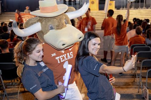 Two incoming students take a selfie with Hook'em, the university's mascot.