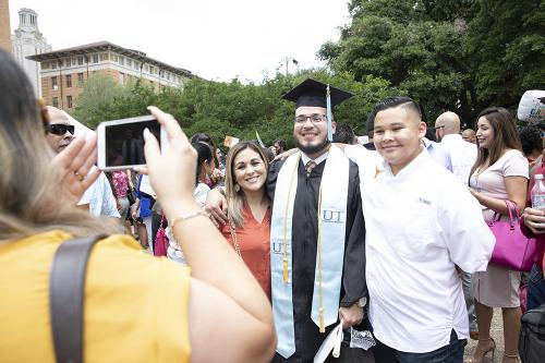 A recent College of Education graduate still wearing his cap and gown poses for a photo with his family.