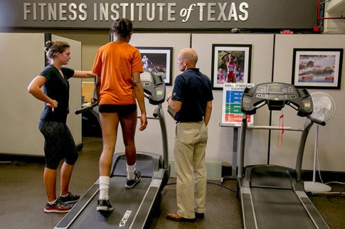 FIT Director Phil Stanforth and a trainer asess an athlete who is jogging on a treadmill.