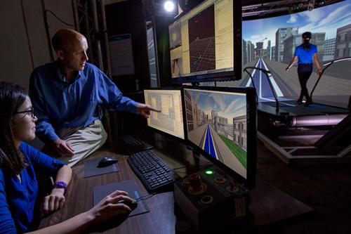 Faculty member Jonathan Dingwell shows a student how to run a VR simulation.