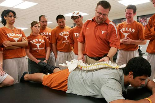 Faculty member Brian Farr demonstrates spinal alignment to a group of students.