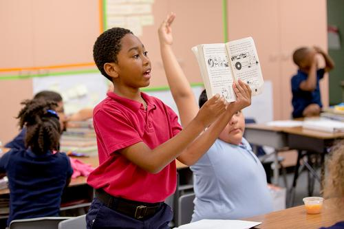 A young black boy talks about a book he is holding up book while standing at his desk.