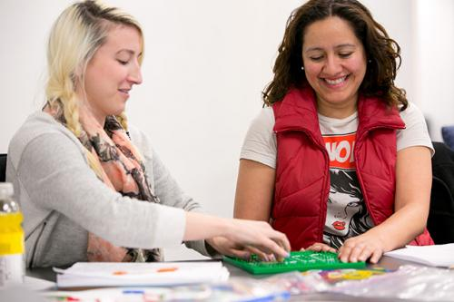 Two students work on a puzzle during a graduate program workshop.