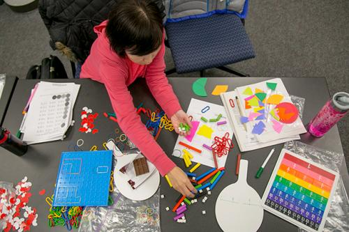 A student organizes materials used with special education students